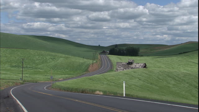 a rural road winds past barns in the green countryside. - palouse stock videos & royalty-free footage