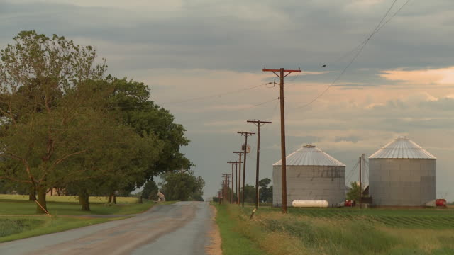 ws rural road with grain elevators in field, newark, illinois, usa - country road stock videos & royalty-free footage