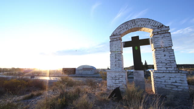 Rural scene in Argentina with a cross at sunset