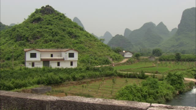 ws rural scene with white house and green mountains, guilin, guangxi zhuang autonomous region, china - guangxi zhuang autonomous region china stock videos & royalty-free footage