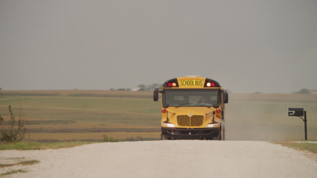 Rural school bus pulls to a stop doors open stop sign young people get on board.