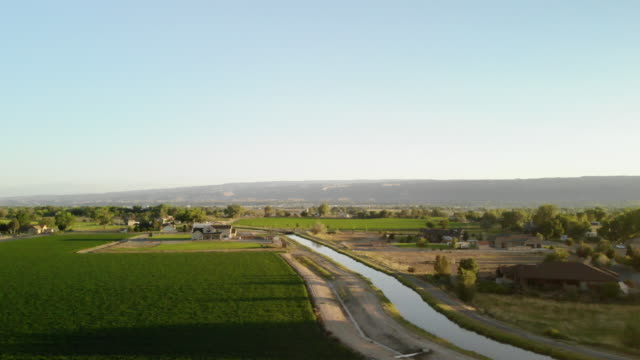 rural western colorado irrigation canal at sunset surrounded by green agricultural fields 4k video - canal stock videos & royalty-free footage