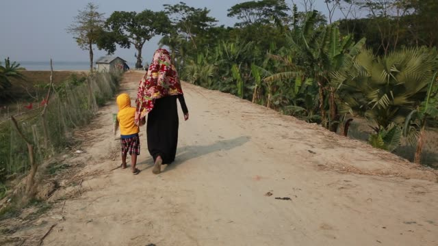 Rural women walk on street taking their child at Dacope Upazila near Sundarban in Khulna District Bangladesh on January 21 2018 The Sundarbans which...