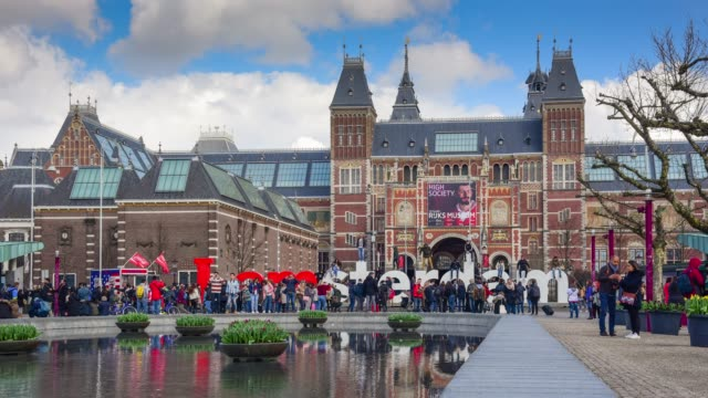 rush hour in amsterdam outside rijksmuseum; tourists walk on the street near sign - colonna architettonica video stock e b–roll