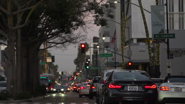 rush hour pedestrian and automobile traffic intersecting on wilshire blvd and rodeo drive at golden hour, los angeles, california - wichita stock videos & royalty-free footage