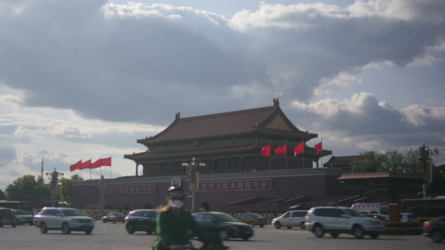 rush hour traffic and police car at the tiananmen square in beijing, china - tiananmen square stock videos and b-roll footage