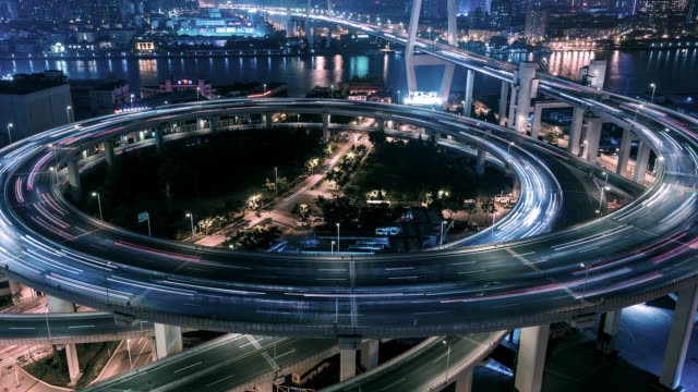 rush hour traffic on multiple highways and flyovers at night / shanghai, china - direzione video stock e b–roll