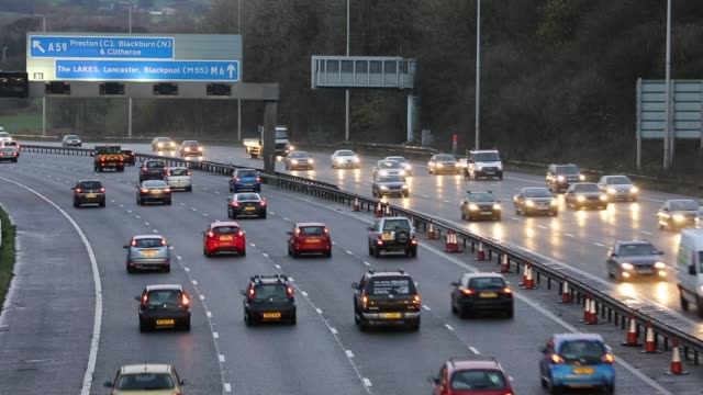rush hour traffic on the m6 motorway near preston, lancashire, uk at dusk. - headlight stock videos & royalty-free footage