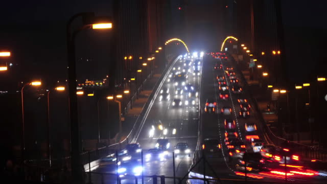 vidéos et rushes de rush hour traffic pouring north over the golden gate bridge in evening fog, which connects the city of san francisco to marin county in the north. - rush hour