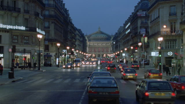 stockvideo's en b-roll-footage met rush hour traffic travels on a busy city street near the paris opera building. - operahuis