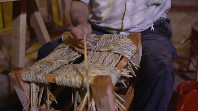 rush seat weaving. view of a man's hands creating a seat for a stool by rolling dampened fibres into a cord and weaving it in a pattern. - weaving stock videos & royalty-free footage