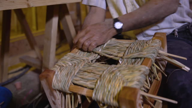 rush seat weaving. view of a man's hands creating a stool by rolling dampened fibres into cords for the traditional technique of rush seat weaving. - stool stock videos & royalty-free footage