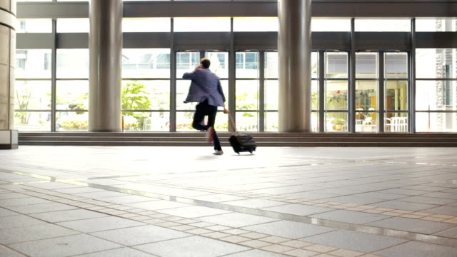 rushing business man running through a japanese office lobby - suitcase stock videos & royalty-free footage