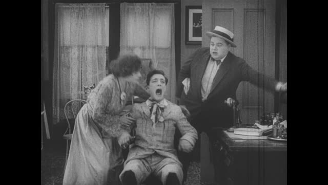 1917 rushing man (fatty arbuckle) becomes annoyed with man (buster keaton) who wails when he throws him in a chair - slapstick comedy stock videos & royalty-free footage