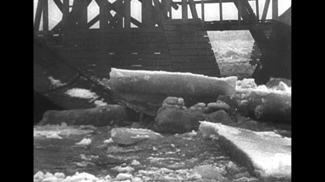 rushing waters, filled with ice chunks, move underneath a section of a temporary bridge in warsaw as a broken section of the bridge can be seen in... - warsaw stock videos & royalty-free footage