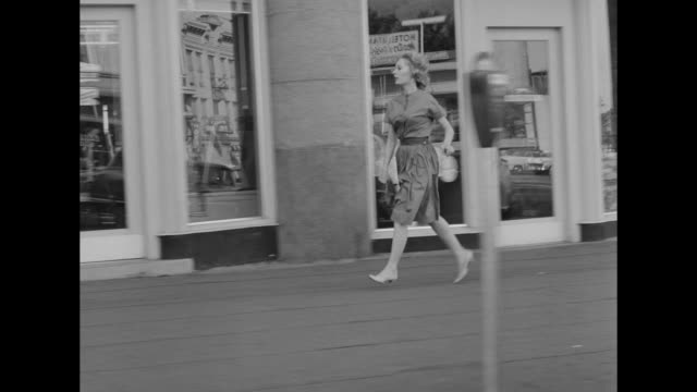 1962 a rushing woman runs through town passing by storefronts - high heels stock videos & royalty-free footage