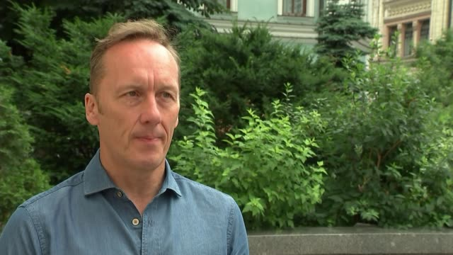 russia 2018 world cup: build-up to england v colombia match; russia: moscow: ext lee dixon interview sot red square: england and colombia fans... - internationaler fußball stock-videos und b-roll-filmmaterial