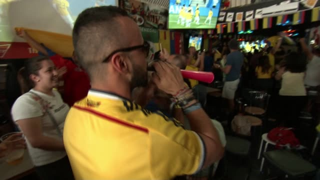 russia 2018 world cup finals: england lose to belgium but qualify for last 16; uk: colombian football fans in bar celebrate as watching tv screens... - television show stock videos & royalty-free footage