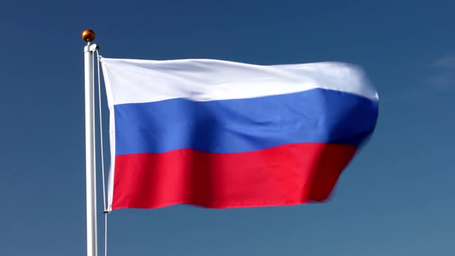 Russia national flag on flagpole with blue sky