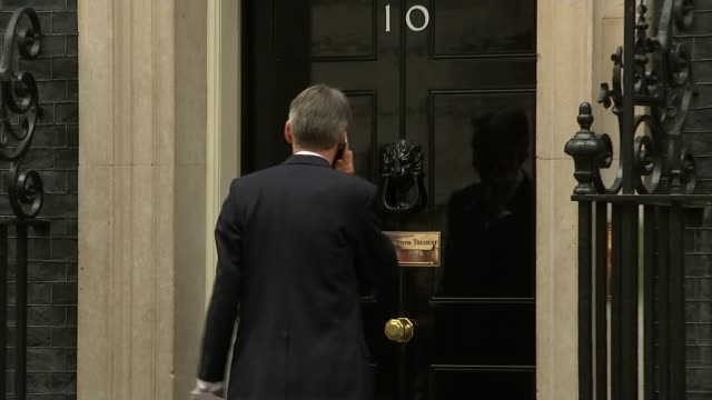 british tourists stranded over bomb fears england london downing street ext philip hammond mp along and into number 10 mobile phone held to his ear /... - kogalymavia flug 9268 stock-videos und b-roll-filmmaterial