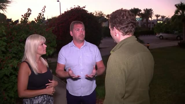 british tourists stranded over bomb fears ext / dusk brendan de garis and abigail de garis interview stand talking with reporter - kogalymavia flug 9268 stock-videos und b-roll-filmmaterial