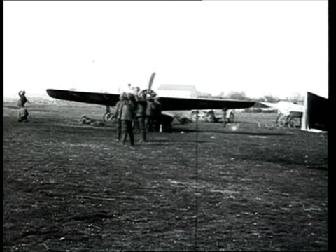 stockvideo's en b-roll-footage met 1915 b/w ws pan russian army aviators working with planes in airfield/ russia - 1915