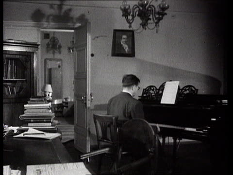 vídeos de stock e filmes b-roll de russian composer dmitri shostakovich getting up from table and sitting down to play piano/ ws ballet dancer galina ulanova performing with partner on... - sentar se