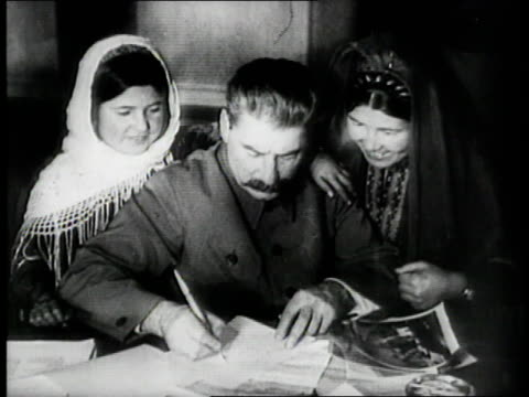 russian dictator joseph stalin signs a document with two peasant women hanging over his shoulders. - former soviet union stock videos & royalty-free footage