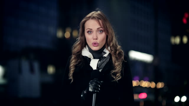 Russian female correspondent reporting live from the city center at night