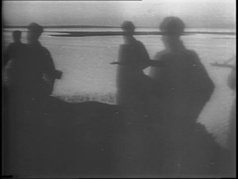 russian forces march in silhouette near water / heavy artillery fire and flashes and explosions at night / a map of russia shows nazioccupied... - 1944 stock videos & royalty-free footage