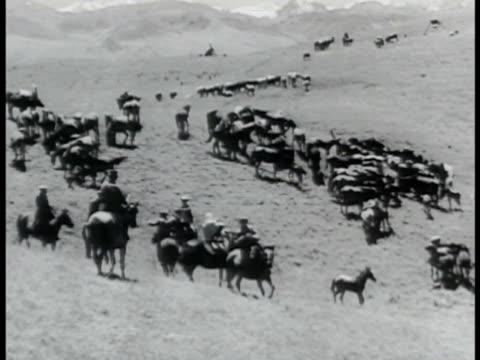 Russian Herdsmen on horseback tending herd of horses men gathered on horseback talking male female peasants looking