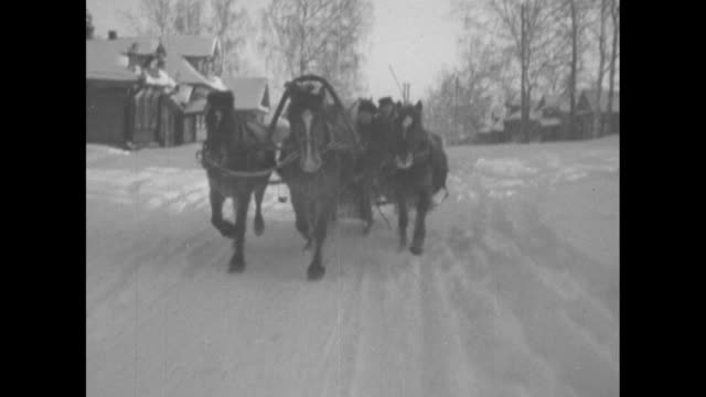 [VO Russian language narration throughout] VS troikas with banner glide across snow / riders bundled against the cold / aerial pan of small town with...