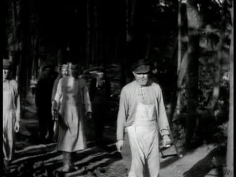vídeos de stock e filmes b-roll de russian males walking on forest road holding saws - 1935