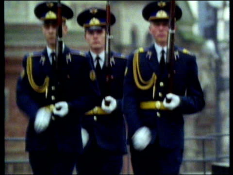 Russian military guards holding rifles and goose stepping tilt down to their booted feet marching Russia