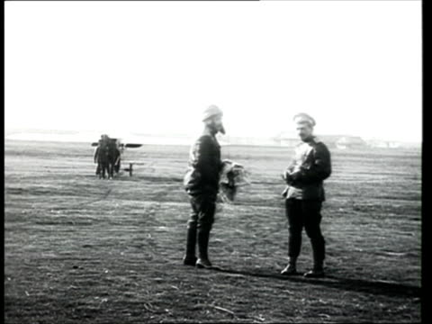 1915 montage b/w ws pan russian military plane making a bumpy landing in airfield/ ws russian aviators hauling small military plane along airfield/ russia - prima guerra mondiale video stock e b–roll