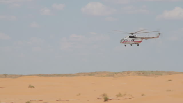Russian military transport helicopter flying low over desert dunes and people
