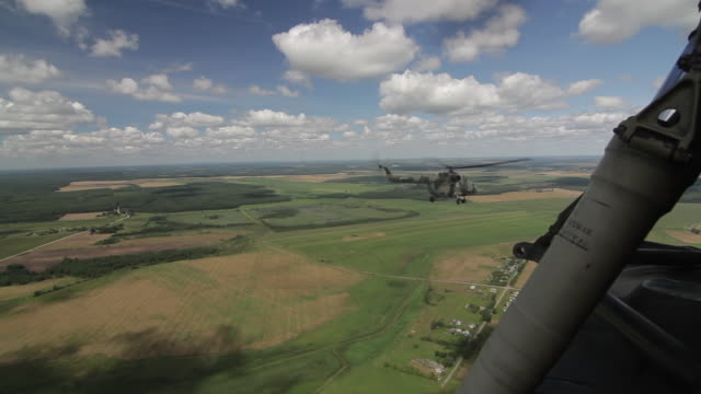 russian military transport helicopter mi-8 flying over the green summer flatland - luftwaffe stock-videos und b-roll-filmmaterial