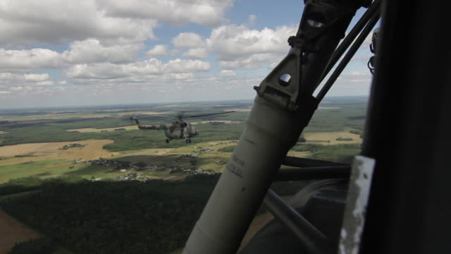 Russian military transport helicopter Mi-8 flying over the green summer flatland