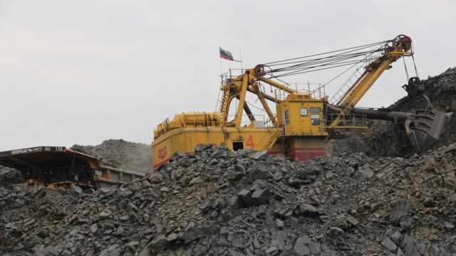 a russian national flag sits on top of an excavator as it collects iron ore from the open pit of the lebedinsky gok iron ore mining and processing... - iron ore stock videos & royalty-free footage