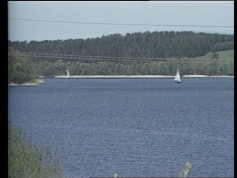b POLAND Mikolajki GV Lake LMS Lake as man fishing outside cabin GV EXT meteorological station PULL OUT to lake