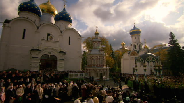 a russian orthodox congregation gathers in the courtyard outside the trinity lavra of st. sergius. available in hd. - congregation stock videos & royalty-free footage