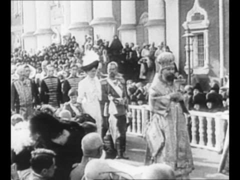 Russian Orthodox priests lead a procession as Czar Nicholas II Czarina Alexandra Feodorovna and their son Czarevich Alexei Nikolaevich follow...