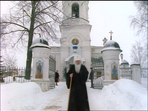 russian priest walking towards camera in snow / st. mother of christ church in background - russian culture stock videos & royalty-free footage