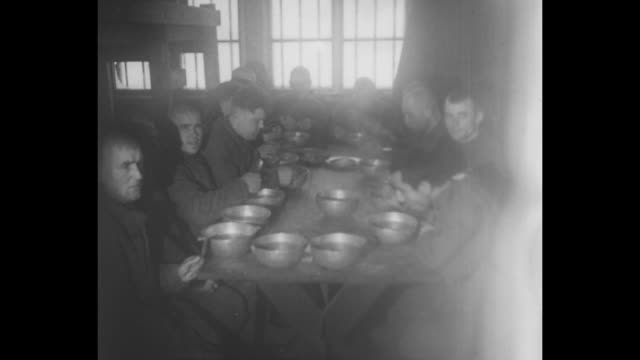 russian prisoners with a dog inside dimly lit barrack, seated on bunk beds, and eating from bowls at a table // men jump from a flatbed truck / men... - prisoner of war stock videos & royalty-free footage
