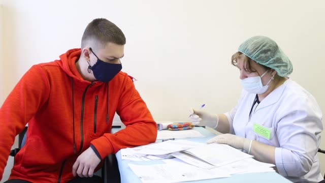 stockvideo's en b-roll-footage met russian recruit wearing face mask as a protective measure is being tested for covid-19 at the entrance to laboratory for being necessarily tested for... - military recruit
