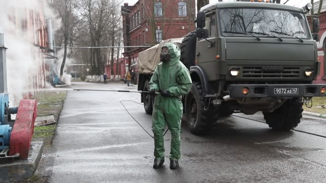 russian soldier wearing protective suit disinfects a territory of a october train factory on april 15, 2020 in saint petersburg, russia - russia点の映像素材/bロール
