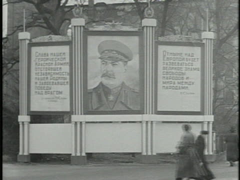 russian soldiers marching by building huge stalin painting billboard w/ russian cyrillic lettering side panels vs soviet officers in coats walking... - 1946 stock-videos und b-roll-filmmaterial