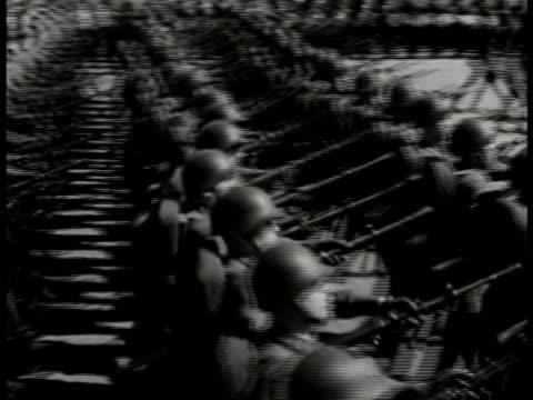 russian soldiers marching w/ rifles pointed forward. single russian tank speeding on city road. many russian soldiers marching. wwii world war ii... - world war ii点の映像素材/bロール