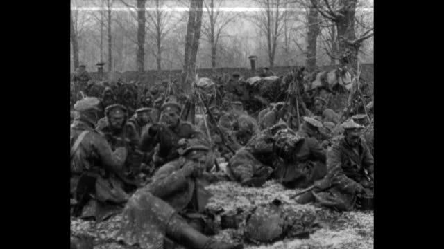 russian soldiers sitting in field eating as it snows / soldiers in line being given food / bodies of russian soldiers being removed from field - polen stock-videos und b-roll-filmmaterial