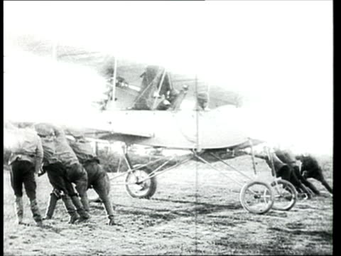 1915 B/W WS Russian soldiers standing against military biplane and ducking to allow for takeoff/ Russia